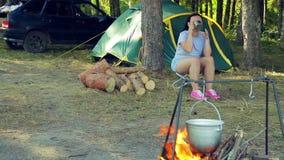 Una giovane donna beve il tè vicino ad una tenda e guarda un giocatore di bocce appendere sopra un fuoco video d archivio