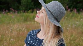 Una giovane donna bionda attraente in un vestito ed in un cappello blu sta sedendosi su un plaid sull'erba il vento soffia i cape video d archivio