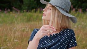Una giovane donna bionda attraente in un vestito ed in un cappello blu sta sedendosi su un plaid sull'erba il vento soffia i cape archivi video