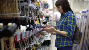 Una giovane donna in una camicia a quadretti blu seleziona un maglio di gomma nel supermercato stock footage