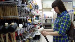 Una giovane donna in una camicia a quadretti blu seleziona un maglio di gomma nel supermercato video d archivio