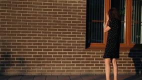 Una giovane donna cammina intorno alla città e smette dalla finestra di esaminare la sua riflessione stock footage