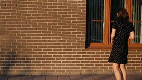 Una giovane donna cammina intorno alla città e smette dalla finestra di esaminare la sua riflessione video d archivio