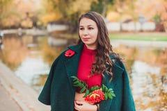 Una giovane donna cammina nel parco di autunno Donna castana che porta un cappotto verde e un vestito rosso immagini stock libere da diritti