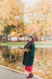 Una giovane donna cammina nel parco di autunno Donna castana che porta un cappotto verde e un vestito rosso fotografia stock libera da diritti