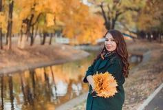 Una giovane donna cammina nel parco di autunno Fa una pausa il lago Donna castana che porta un cappotto verde immagini stock