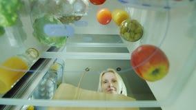 Una giovane donna carica l'alimento nel frigorifero Apre la porta del frigorifero e mette là appena le verdure comprate stock footage