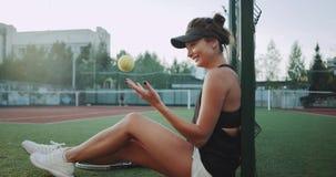 Una giovane donna carismatica dopo il gioco ha una rottura che si siede sul pavimento e che gioca con una pallina da tennis, sorr archivi video