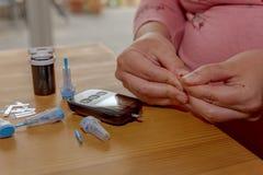 Una giovane donna a casa controlla la sua glicemia fotografia stock