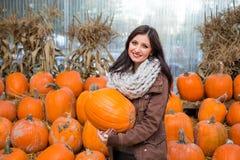 Una giovane donna castana che tiene una zucca davanti ad una fila delle zucche su un'azienda agricola fotografia stock libera da diritti