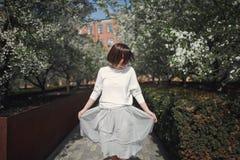 Una giovane donna castana sorridente graziosa con i capelli di scarsità in vestiti romantici leggeri balla in un parco sbocciante fotografia stock libera da diritti