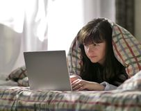 Una giovane donna castana sta trovandosi sotto una coperta e sta scrivendo in un computer portatile fotografia stock libera da diritti