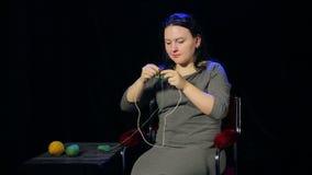 Una giovane donna castana su un fondo nero tricotta sugli aghi dal filo verde stock footage