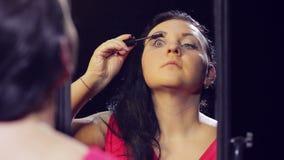 Una giovane donna castana in un vestito rosso davanti ad uno specchio fa il trucco dell'occhio con mascara nera stock footage