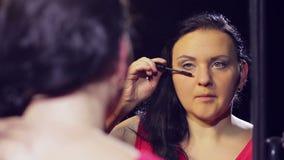 Una giovane donna castana in un vestito rosso davanti ad uno specchio mette la mascara sui suoi cigli archivi video