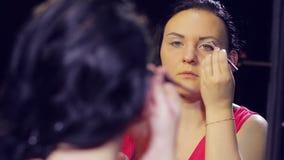 Una giovane donna castana in un vestito rosso davanti ad uno specchio mette le ombre luminose sulle sue palpebre stock footage