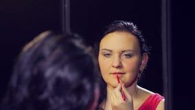 Una giovane donna castana in un vestito rosso davanti ad uno specchio si applica un contorno rosso alle sue labbra video d archivio