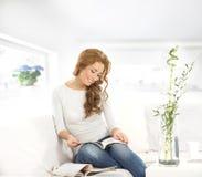 Una giovane donna caucasica che legge un libro su un sofà immagine stock