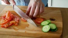 Una giovane donna che è cucinante e tagliente i pomodori freschi per insalata sul tagliere video d archivio