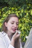 Una giovane donna che applica un lipstic Immagini Stock Libere da Diritti