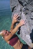 Una giovane donna che arrampica in su un fronte della roccia Fotografia Stock