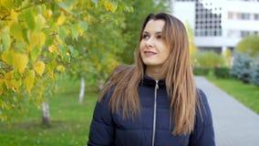 Una giovane donna che cammina lungo il vicolo di autunno del parco della città Movimento lento 4k 60fps del ritratto La ragazza c stock footage
