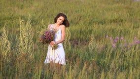 Una giovane donna che cammina sul campo verde con il mazzo e sorridere del fiore archivi video