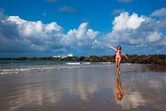 Una giovane donna che cammina sulla spiaggia dell'oceano Immagine Stock