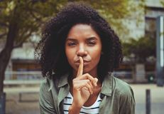Una giovane donna che fa gesto di silenzio fotografia stock