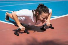 Una giovane donna che fa i piegamenti sulle braccia fuori, esaurito immagine stock