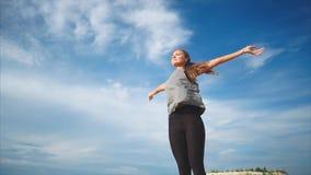 Una giovane donna che fa un esercizio respirante isolato in vento fresco della natura la soffia archivi video