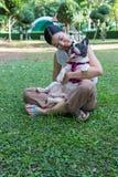 Una giovane donna che gioca con un bulldog francese fotografia stock