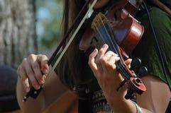 Una giovane donna che gioca il violino. Fotografie Stock