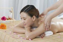 Una giovane donna che gode del massaggio Immagini Stock