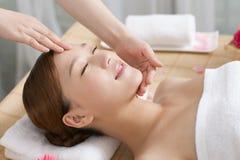 Una giovane donna che gode del massaggio alla stazione termale Fotografia Stock