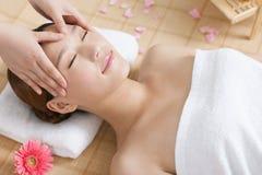 Una giovane donna che gode del massaggio alla stazione termale Immagini Stock