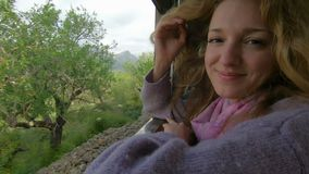 Una giovane donna che gode del viaggio su un treno vecchio, pieno d'ammirazione le belle posizioni turistiche video d archivio