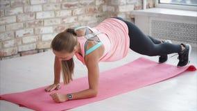 Una giovane donna che ha una costituzione fisica sportiva va dentro per gli sport nel club di forma fisica archivi video