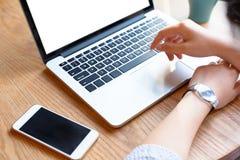 Una giovane donna che lavora con il computer portatile e lo smartphone Fotografie Stock Libere da Diritti