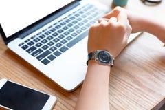 Una giovane donna che lavora con il computer portatile e lo smartphone Immagini Stock