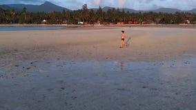 Una giovane donna che pareggia alla spiaggia sul tramonto colpo aereo del fuco, movimento lento archivi video