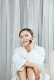 Una giovane donna che parla dal telefono cellulare nel salone della stazione termale Fotografia Stock