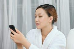 Una giovane donna che parla dal telefono cellulare nel salone della stazione termale Immagini Stock