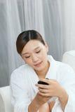 Una giovane donna che parla dal telefono cellulare nel salone della stazione termale Fotografie Stock