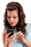 Una giovane donna che per mezzo dello Smart Phone Immagine Stock