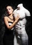 Una giovane donna che posa con un manichino Fotografia Stock