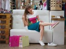 Una giovane donna che prova su un paio degli stivali rosa-chiaro su un fondo del deposito Ragazza affascinante che sceglie le sca fotografie stock