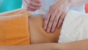 Una giovane donna che riceve un massaggio Massaggio dello stomaco Vista laterale archivi video
