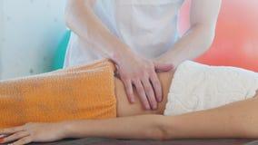 Una giovane donna che riceve un massaggio Un massaggiatore che massaggia lo stomaco stock footage