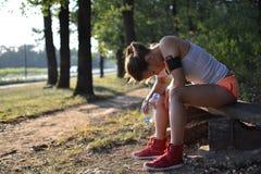 Una giovane donna che riposa dopo l'allenamento Fotografia Stock Libera da Diritti